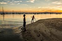 Silhueta de crianças à beira da água na Praia de Santo Antonio de Lisboa. Florianópolis, Santa Catarina, Brasil. / Silhouette of children by the sea at Santo Antonio de Lisboa Beach. Florianopolis, Santa Catarina, Brazil.