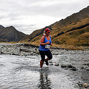 Runner Erin Frisby crosses  Moke Creek on the Ben Lomond High Country Station during the Pure South Shotover Moonlight Mountain Marathon and trail runs. Moke Lake, Queenstown, New Zealand. 4th February 2012. Photo Tim Clayton