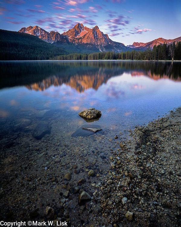 The sun slowly rises over the Sawtooths and the still waters of Stanley Lake, ID.