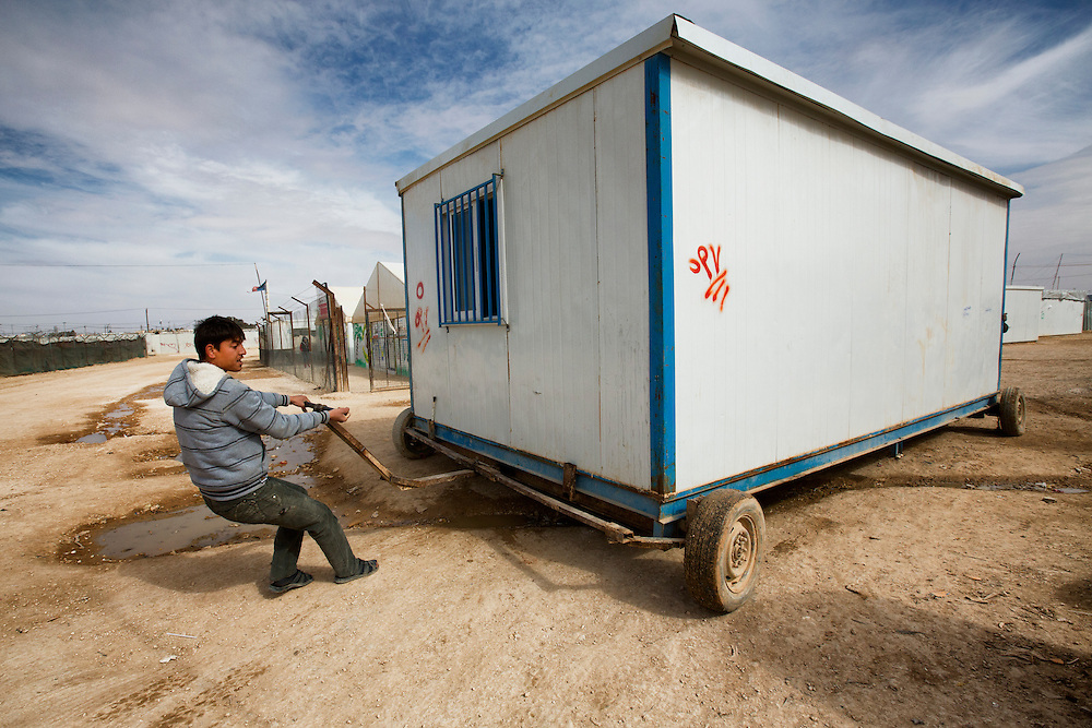 "A man moves a pre-fabricated trailer known as a ""Caravan"" into position. These are becoming more commonplace, replacing tents as a primary dwelling. Feb. 6, 2014. Zaatari Camp, Jordan. (Photo by Gabriel Romero/Alexia Foundation ©2014)"