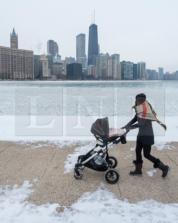 © Licensed to London News Pictures. 21/12/2016. Chicago, USA. A woman pushes a pram in Milton Olive Park. After several days of extremely low temperatures, a frozen Lake Michigan, off Lake Shore Drive in Chicago, is seen on the day of the winter solstice. Photo credit : Stephen Chung/LNP