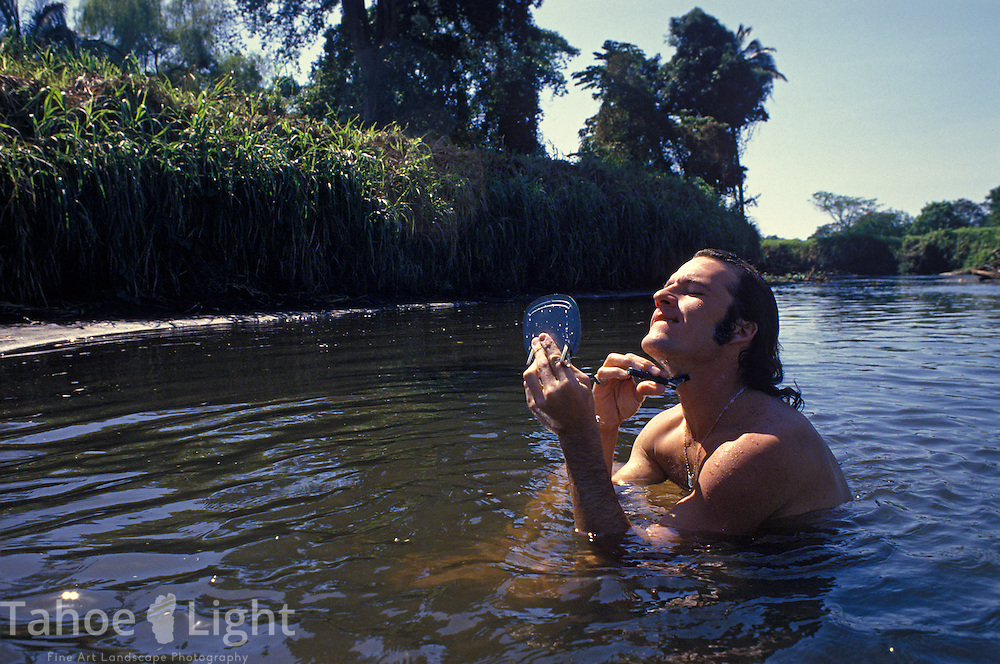 Dan Cearley shaves in the river near a sugar cane field in southern Guatemala.