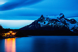 A lodge reflected on a lake at dusk, Torres del Paine, Chile, South America
