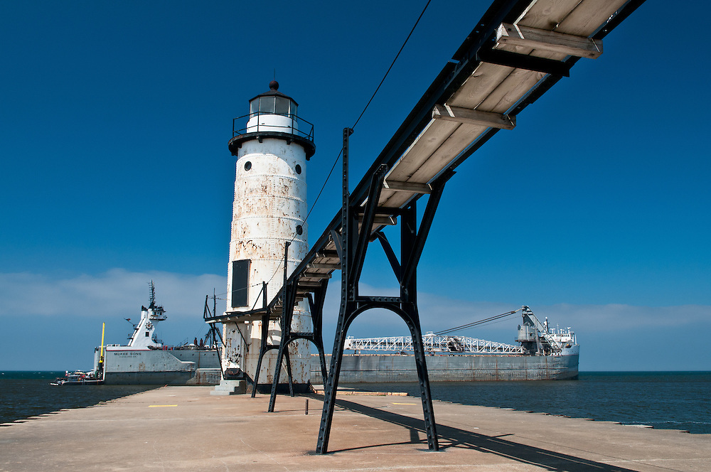 The old white tower and The McKee Sons Freighter, which ran aground when leaving the harbor on this day.<br /> Manistee, Michigan