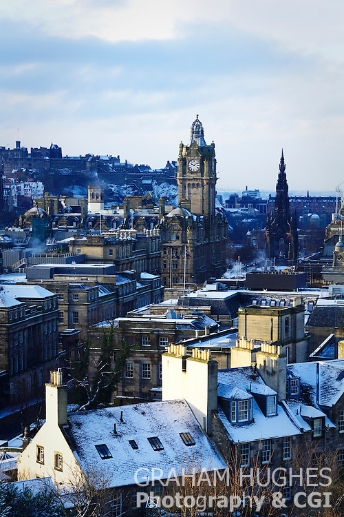 Edinburgh rooftops with snow and Balmoral Hotel in background.