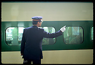 Green & yellow stripes of bullet train frame stationmaster as he points for departure; Utsunomiya Japan