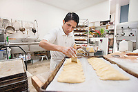 Young man preparing dough in bakery kitchen