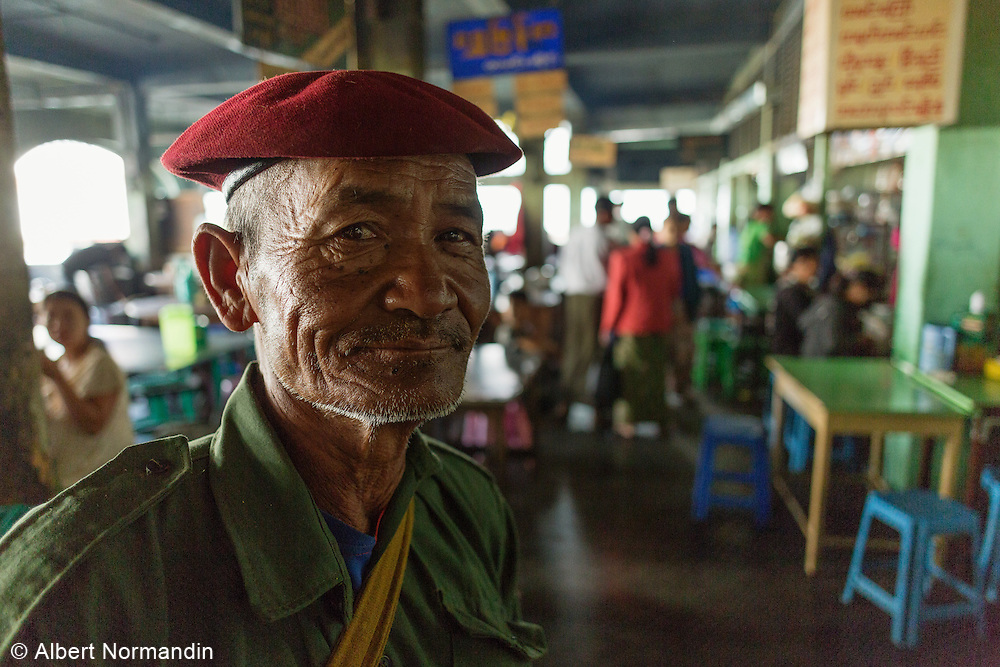 Older man smiles and stand around, with red beret in City Market restaurant, Taunggyi