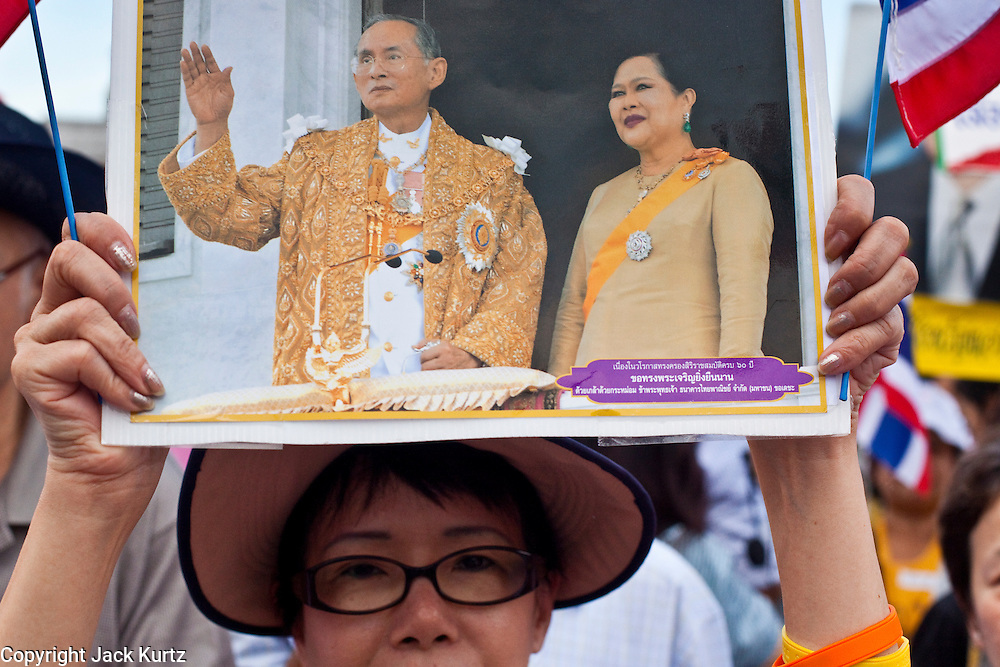 "Apr. 18, 2010 - Bangkok, Thailand: A Pink Shirt holds up a photo of Thai King Bhumibol Adulyadej during a peace rally Sunday. Thousands of so called ""Pink Shirts"" jammed the area around Victory Monument in Bangkok to show support the Thai Monarch, King Bhumibol Adulyadej, and against the Red Shirts, who are demonstrating just a few kilometres away in the Ratchaprasong area. The Pink Shirts claim to not support either of the other political factions who wear colors - the Red Shirts, who support deposed Prime Minister Thaksin Shinawatra and their opponents the Yellow Shirts, who are against Thaksin.    Photo By Jack Kurtz"