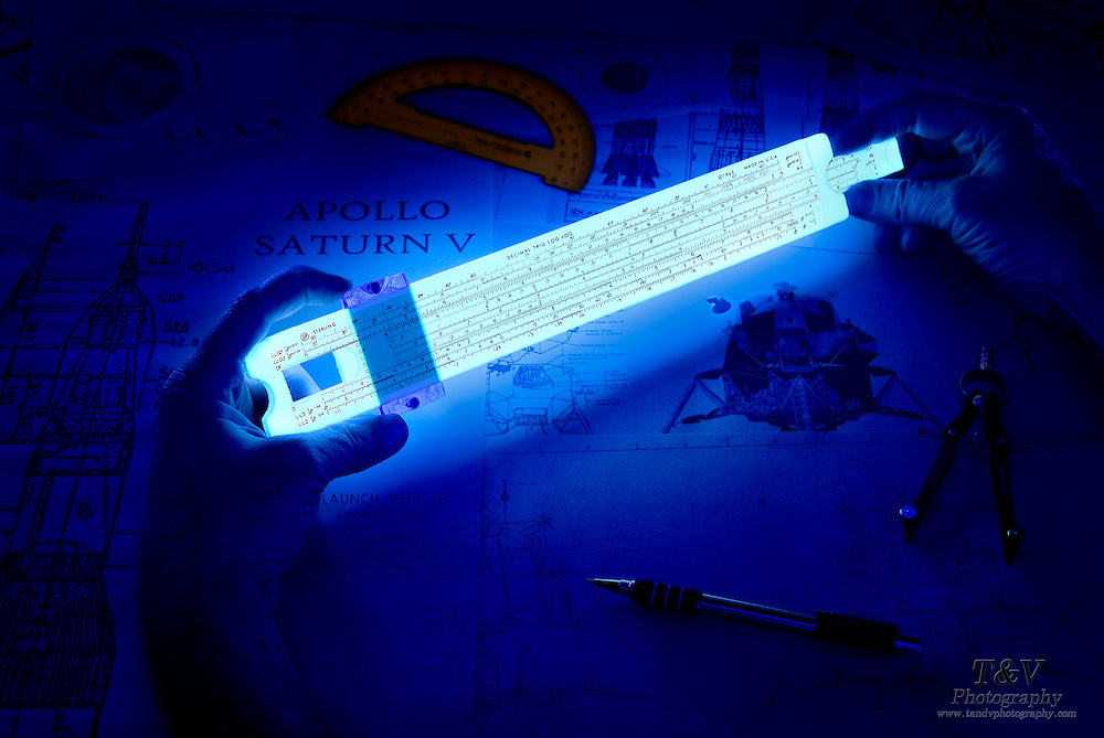 Hands adjust a glowing slide rule over blueprints for the Apollo Saturn V rocket and Lunar Module.Black light