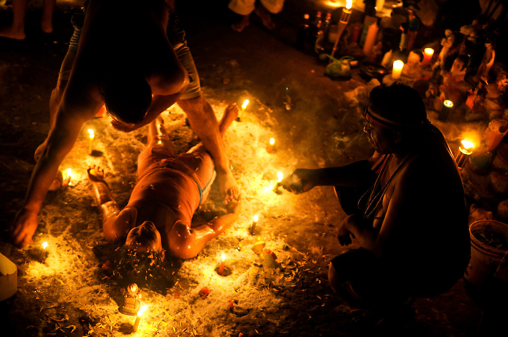 A family from Caracas performs a ritual asking various saints to bless their children with evolution, health, well being and education. As the children lay surrounded by candles, intricate chalk patters and flowers, the adult family members beat drums and chanted, smoked cigars and poured flower petals and perfumes on their children.