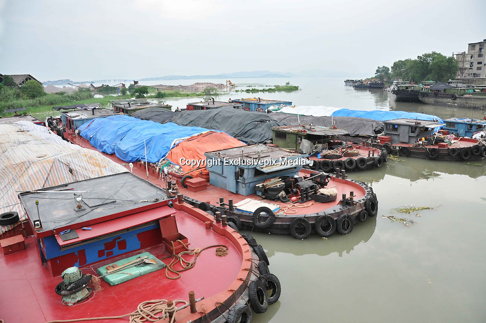 SUZHOU, CHINA - JULY 04: <br /> Ships carrying waste berth at a dock in the Taihu National Tourism Vacation Zone on July 4, 2016 in Suzhou, Jiangsu Province of China. Police seized 8 ships which loaded about 4,000 tons of suspected household garbage from Shanghai and arrived at a dock in Suzhou on July 1. Over 20,000 tons of waste was found on the bank within a drug rehabilitation center at the Suzhou Taihu National Tourism Vacation Zone.<br /> &copy;Exclusivepix Media