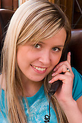 ICE.MWdrv04.54.xrw..Thordis Björnsdottir, 17 on the phone at her parent's home in Hafnarfjördur, Iceland, near Reykjavik. She has dropped out of school and gotten a job. Ten years ago she and her family were the Icelandic participants in Material World: A Global Family Portrait, 1994 for which they took all of their possessions out of their house for a family and possessions portrait in the snow. Pages 162-163. Phone, Mobile, Telephone. {{Central image from original book project is: ICE.mw.01.xxs.}}