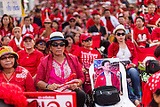 10 MAY 2014 - BANGKOK, THAILAND: A Red Shirt supporter holds a chair with a photo of ousted Prime Minister Thaksin Shinawatra. Thaksin is revered by many in the Red Shirt movement. Thousands of Thai Red Shirts, members of the United Front for Democracy Against Dictatorship (UDD), members of the ruling Pheu Thai party and supporters of the government of ousted Prime Minister Yingluck Shinawatra are rallying on Aksa Road in the Bangkok suburbs. The government was ousted by a court ruling earlier in the week that deposed Yingluck because the judges said she acted unconstitutionally in a personnel matter early in her administration. Thailand now has no functioning government. Red Shirt leaders said at the rally Saturday that any attempt to impose an unelected government on Thailand could spark a civil war. This is the third consecutive popularly elected UDD supported government ousted by the courts in less than 10 years.    PHOTO BY JACK KURTZ