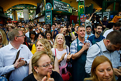 © Licensed to London News Pictures. 14/06/2017. London, UK. Traders and shoppers celebrate the reopening of Borough Market in London as the market bell is rung on 14 June 2017, following a terror attack that killed 8 people over a week ago. Photo credit: Tolga Akmen/LNP