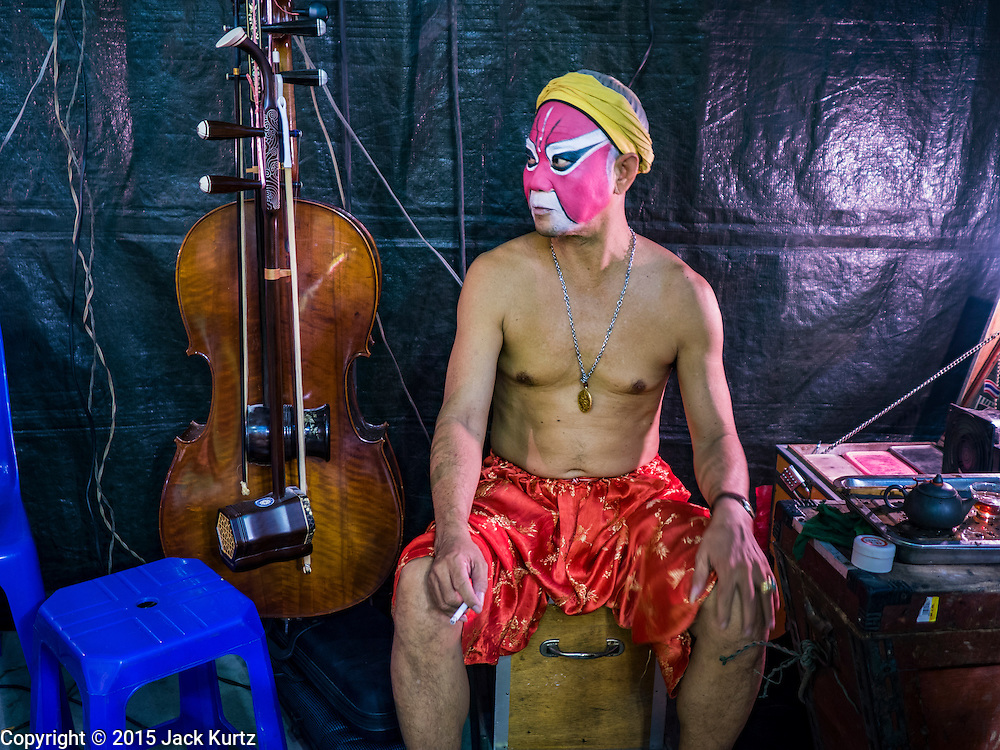15 OCTOBER 2015 - BANGKOK, THAILAND:  A Chinese opera performer smokes a cigarette backstage before an opera performance at the Vegetarian Festival at the Joe Sue Kung Shrine in the Talat Noi neighborhood of Bangkok. The Vegetarian Festival is celebrated throughout Thailand. It is the Thai version of the The Nine Emperor Gods Festival, a nine-day Taoist celebration beginning on the eve of 9th lunar month of the Chinese calendar. During a period of nine days, those who are participating in the festival dress all in white and abstain from eating meat, poultry, seafood, and dairy products. Vendors and proprietors of restaurants indicate that vegetarian food is for sale by putting a yellow flag out with Thai characters for meatless written on it in red. The shrine is famous for the Chinese opera it hosts during the Vegetarian Festival. The operas are free.   PHOTO BY JACK KURTZ