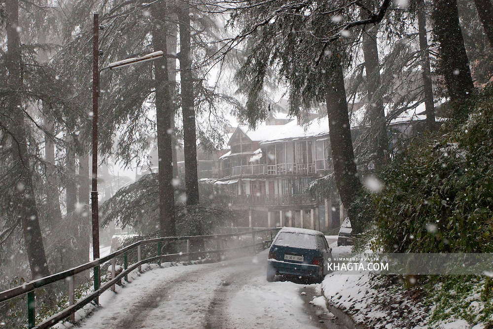 A car covered in snow, parked somewhere in jakhu during the seasons first snowfall in Shimla, Western Himalayas