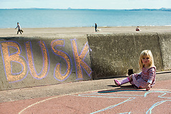 A mile of buskers on Portobello Prom this afternoon in the nonth annual Big Beach Busk. The day starts with the man who first came up with the idea for the busk, ?Paul Lambie and his team of local helpers chalking out the circular 'pittches' all along the Prom. And then the buskers arrive - all ages, all styles of music, from solo performers to big bands. The place is heaving! A young helper.<br /> <br /> <br /> © Jon Davey/ EEm