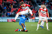 Doncaster Rovers midfielder Kieran Sadlier (22) rides this challenge from Peterborough Utd forward Ivan Toney (17) during the EFL Sky Bet League 1 match between Doncaster Rovers and Peterborough United at the Keepmoat Stadium, Doncaster, England on 9 February 2019.