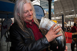 Olympia, London, August 12th 2014. A visitor to CAMRA's Great British Beer Festival examine's a Viking drinking horn at one of the many independent traders' stands.