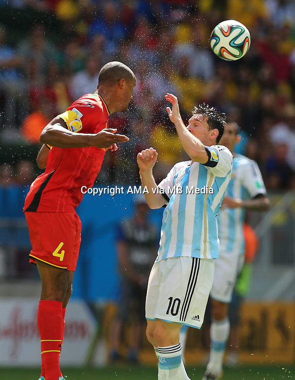 Sweat flies off Vincent Kompany of Belgium as he heads past Lionel Messi of Argentina