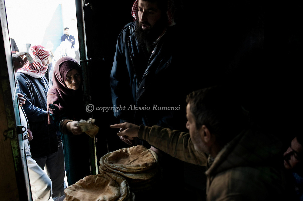 SYRIA - Al Qsair. A woman buy some bread in of one of the three groceries in Al Qsair, on January 29, 2012. Al Qsair is a small town of 40000 inhabitants, located 25Km south-west of Homs. The town is besieged since the beginning of November and so far it counts 65 dead. ALESSIO ROMENZI