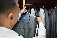 Tailor measuring shoulder of the suit
