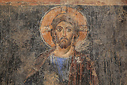 Detail of fresco of Christ with crucifix halo and book, with hand raised in gesture of blessing, from the Church of Labova e Kryqit, or church of the Holy Cross, dedicated to St Mary, one of the oldest churches in Albania, mainly 13th century although with Byzantine foundations of 527-565 AD in the time of Emperor Justinian, Labova e Kryqit, Gjirokastra, Albania. The nave and aisle form a cruciform plan and the high central cupola is typically Byzantine. The interior walls are covered with 9 levels of frescoes. Picture by Manuel Cohen