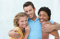Young man with arms round two female friends portrait