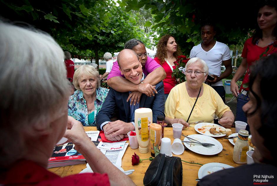 Dordrecht - Een vrouw omhelst diederik Samsom onverwacht tijdens het gesprek aan tafel van de BBQ.PvdA Lijsttrekker Diederik Samsom ging op campagne in Dordrecht, hij ging rozenuitdelen in winkelcentrum Sterrenburg en bezocht de buurtbarbecue op het Dalmeyerplein in Dordrecht. Foto: Phil Nijhuis