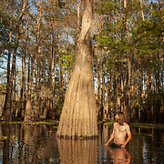 """Cypress tree """"salvage pirate"""" and furniture builder, Hamilton Hall, searches for old cypress logs in the Atchafalaya Basin by feeling the swamp floor with his feet. Hall finds and recovers cypress woods from logging days and builds furniture with the logs. It is illegal to cut down cypress trees now -- so the wood, found by scavengers such as Hall, is a rare commodity."""