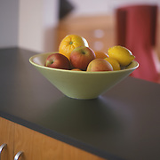 Green vase of Architectural Pottery with oranges and apples in it resting on a black kitchen counter top. the background is out of focus.
