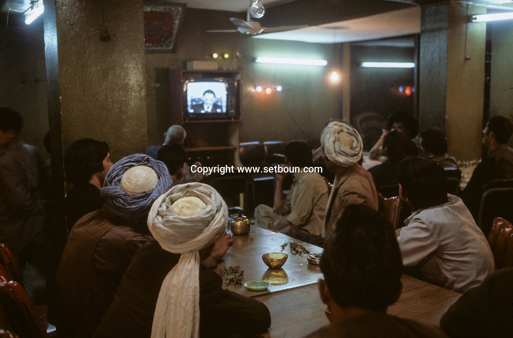 Afghanistan. the communist regime  / after the coup d 'etat of Afizoulah Amin against Taraki / people gather in a cafe to watch the new leader on TV /   kabul  Afghanistan  / Le regime communiste. Apres le coup d etat de Afizoulah Amin contre Taraki. les gens decouvrent le nouveau leader communiste a la television  Kaboul  Afghanistan  / nb 26700 24 / 26700 / L0055657