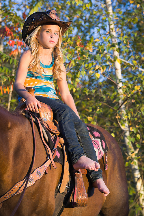 Young blonde cowgirl on her horse in late evening golden light, sitting casually while barefoot and wearing cowboy hat, Pennsylvania, PA, USA.
