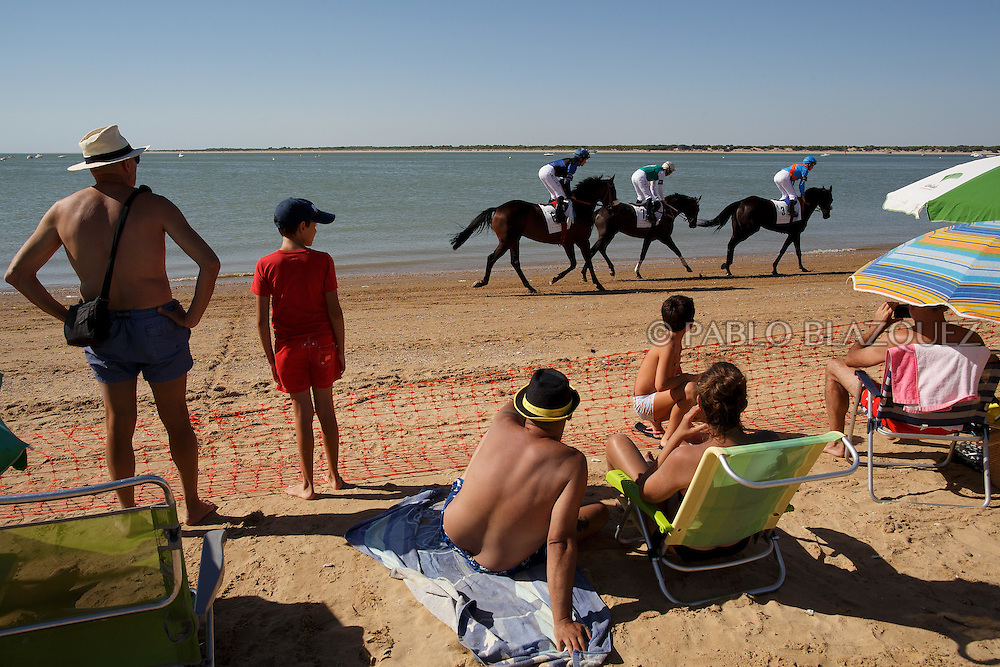 12/08/2016. Jockeys ride their horses along the beach during the beach horse races on August 12, 2016 in Sanlucar de Barrameda, Cadiz province, Spain. Sanlucar de Barrameda yearly horse races traditional origin started with informal races of horse's owners delivering fish from the port to the markets. But the first formal races date back to 1845 and they are the second oldest in Spain, after Madrid. The horse races take place near the Guadalquivir river mouth during August