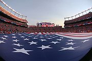 A large American flag covers the field during the playing of the National Anthem in this wide angle, general view photograph taken before the Denver Broncos 2016 NFL week 1 regular season football game against the Carolina Panthers on Thursday, Sept. 8, 2016 in Denver. The Broncos won the game 21-20. (©Paul Anthony Spinelli)