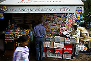 A woman walks past as a customer browses at a newsstand in Defence Colony market, New Delhi, where Indian and Indian versions of international magazines are displayed for sale on 18 September 2008. Photo : Suzanne Lee for The National.