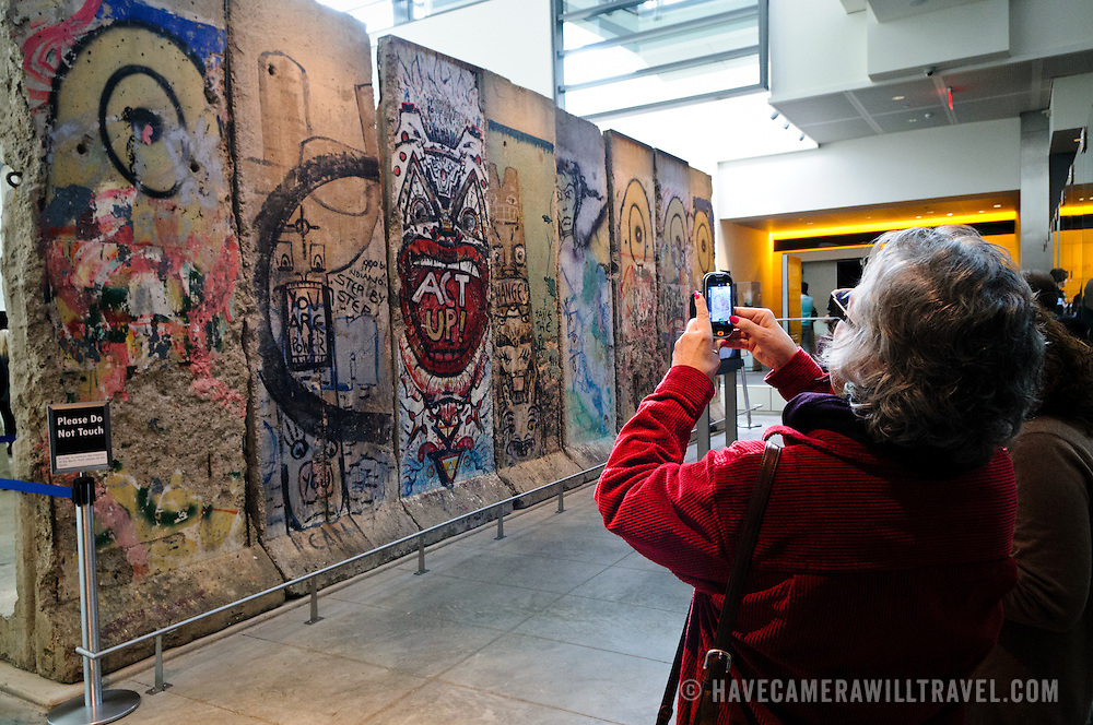 Tourists use a smartphone to take a photo of the large section of the Berlin Wall at the Newseum in Washington DC. The Newseum is a 7-story, privately funded museum dedicated to journalism and news. It opened at its current location on Pennsylvania Avenue in April 2008.