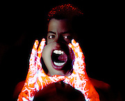 Boy with glowing hands holding a magnifying lens in front of his face as he yells.Black light