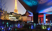 Quai Branly Museum, 2007, by architect Jean Nouvel, Paris, France. View From bridge-like long gallery to Eiffel Tower reflecting the coloured lights in the garden and showing surrounding buildings. Picture by Manuel Cohen.