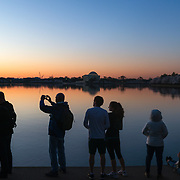Spectators watch and take pictures as the sun begins to rise over a cherry blossom filled Tidal Basin in Washington, D.C.