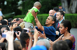 President Barack Obama holds up a baby as he greets members of his staff and armed servicemen and women at an Independence Day barbeque on the South Lawn of the White House in Washington, DC, USA on July 4, 2011. Photo by Kevin Dietsch/Pool/ABACAPRESS.COM  | 281784_009 Washington Etats-Unis United States