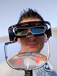 Man looking at 3D television through 3D glasses at Photokina digital imaging trade show in Cologne Germany 2010
