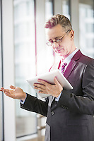 Businessman gesturing while using tablet PC in office