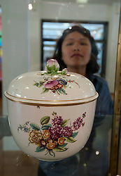 Visitor looking at porcelain vase at the Gemeentemuseum in The Hague, Den Haag,  Netherlands