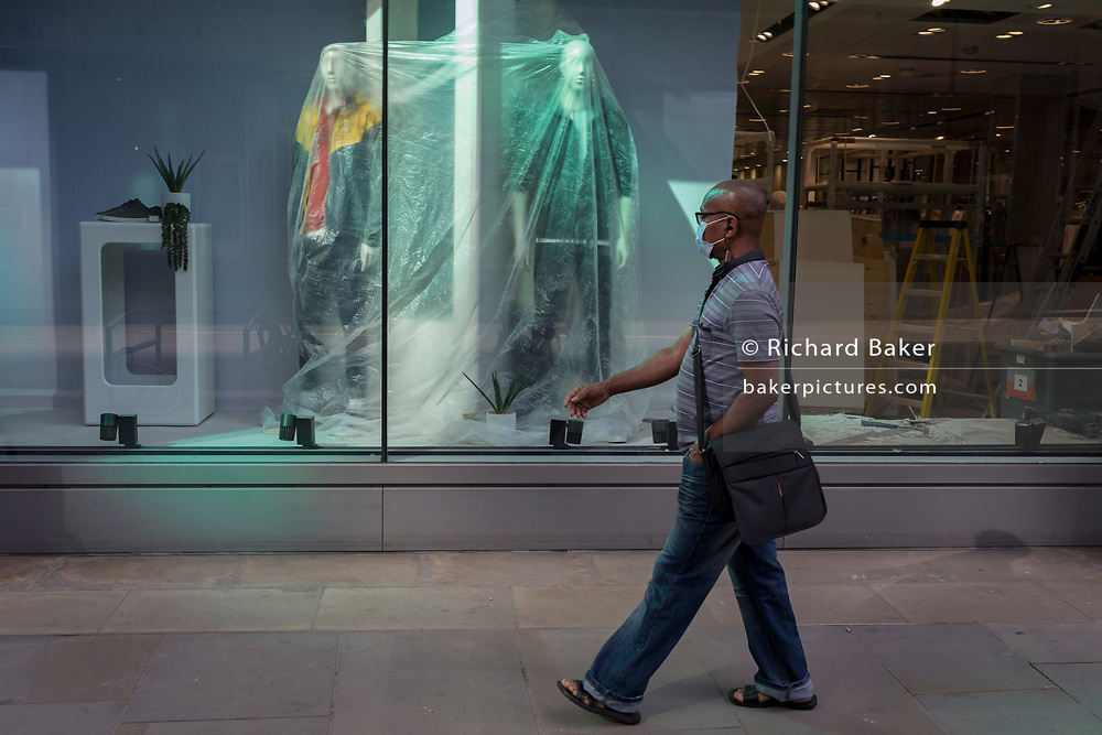 Ten weeks after the UK went into Coronavirus pandemic lockdown, the Office for National Statistics reveal that the total death toll has passed 50,000 covid-19 victims, a Londoner wearing a face mask walks past clothing mannequins in the shop window of a retailer undergoing extensive refurbishment, are covered in a protective layer of plastic, in the City of London, the capital's financial district, on 2nd June 2020, in London, England. The retail industry has taken advantage of quiet roads during lockdown, as an opportunity to have repairs and refurbs caried out in their premises.
