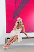 Full length of smiling young woman having conversation on mobile phone with painting in background