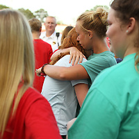 Dianna Lowry, 16, left, gets a hug from Nettleton High School teacher Brandie Williams before the candlelight vigil for Maggie Riley and Brandon Coward who were killed in a car accident over the weekend.