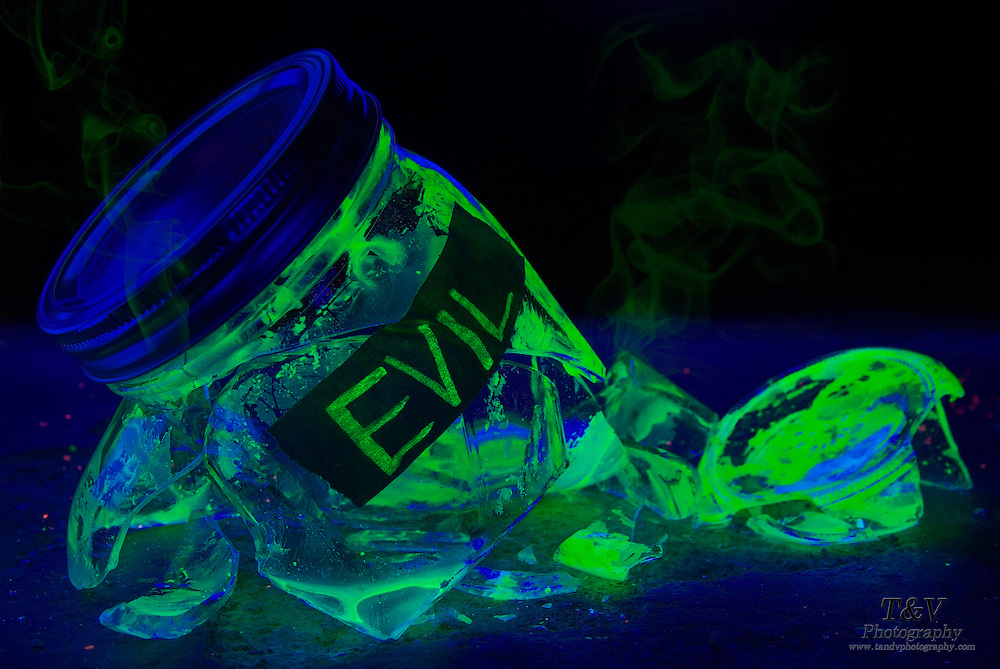 "A glowing mason jar labeled ""Evil"" lies broken on a cement floor as green smoke escapes from its  glass fragments.Black light"