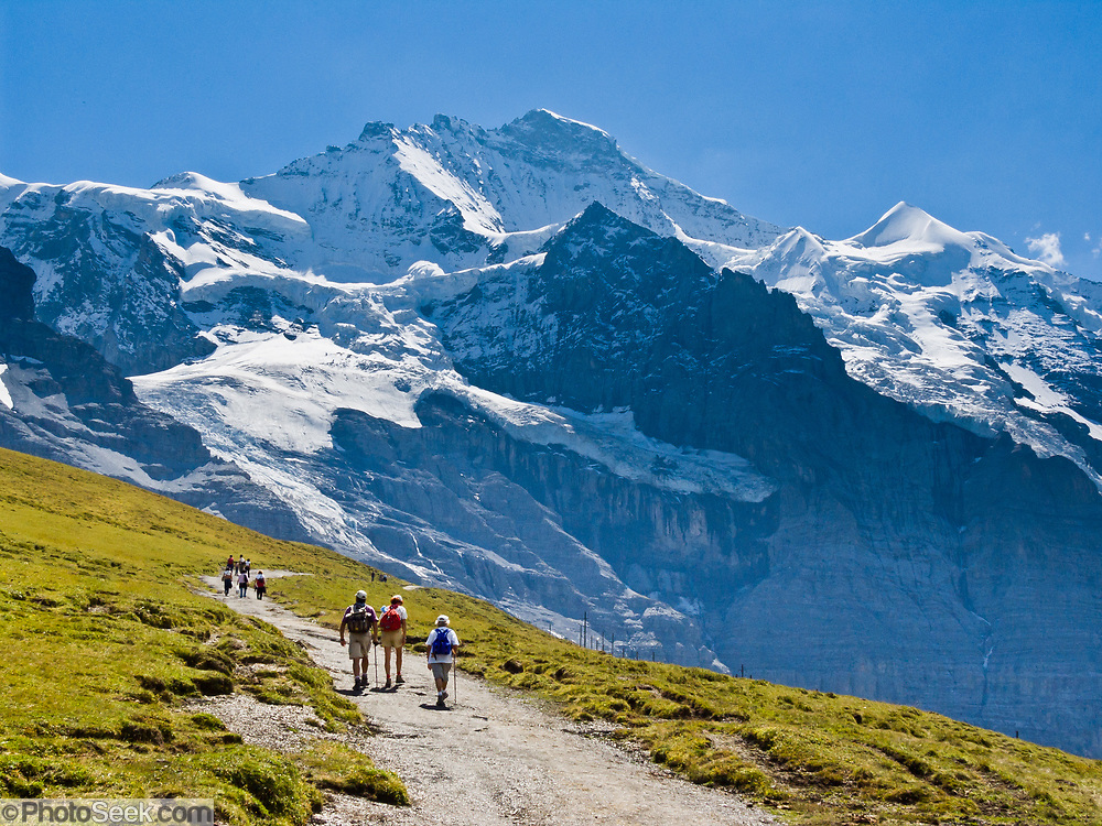 "Hike at Kleine Scheidegg towards the icy peak of Jungfrau (4158 meters or 13,642 feet) in the Berner Oberland, Switzerland, the Alps, Europe. The Bernese Highlands are the upper part of Bern Canton. UNESCO lists ""Swiss Alps Jungfrau-Aletsch"" as a World Heritage Area (2001, 2007)."